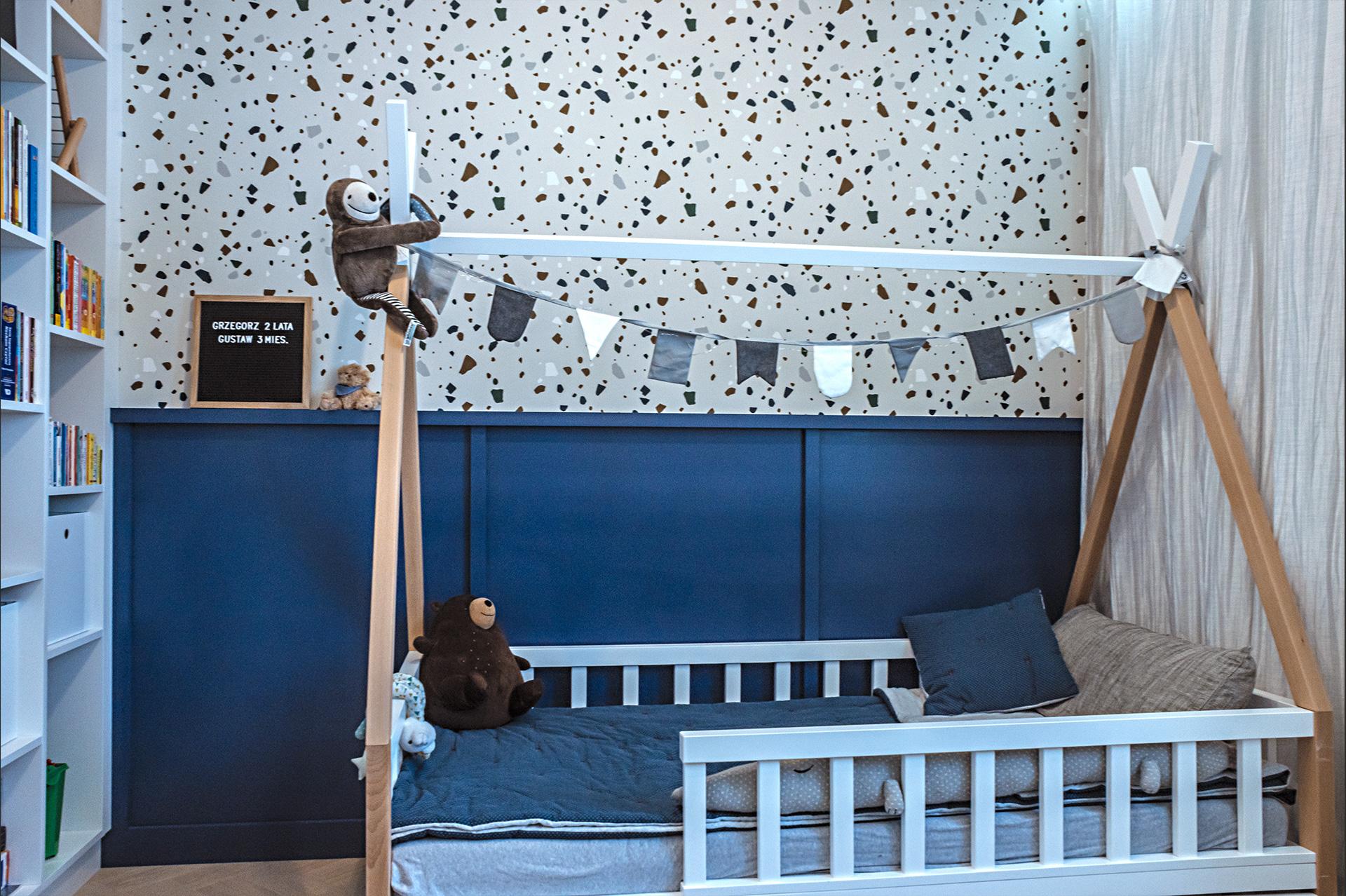 Ponad boazerią pokoju dziecięcego – tapeta z wzorem terazzo o odpowiedniej palecie barwnej.