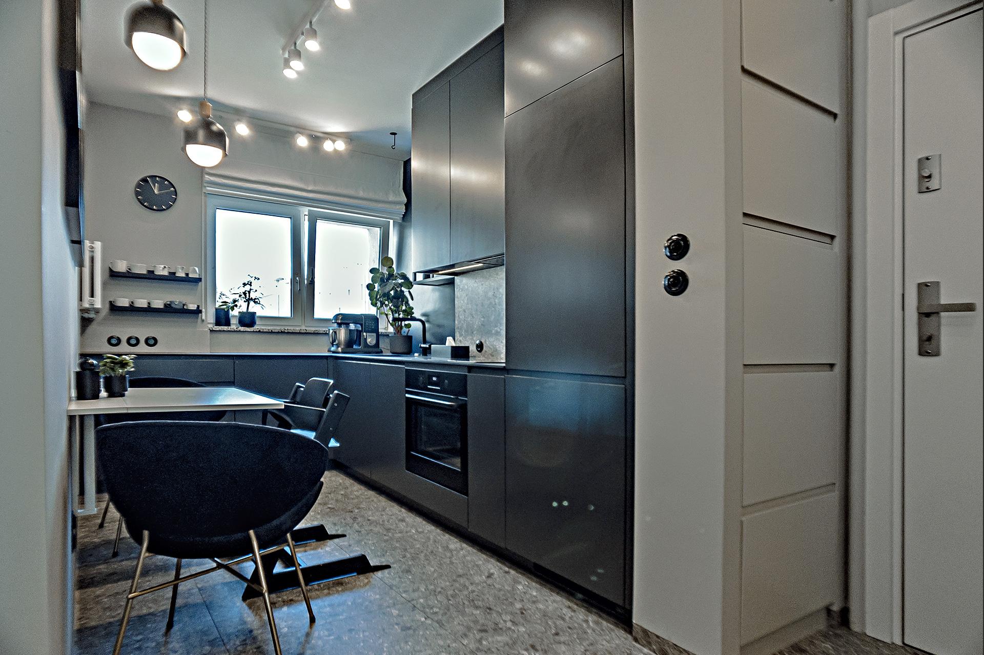 Dzięki wyburzeniu ściany między kuchnią i korytarzem, optycznie powiększyłyśmy niewielkie wnętrze. Tuż przy wejściu – szafki na obuwie wbudowane w pozostawioną resztkę ściany.