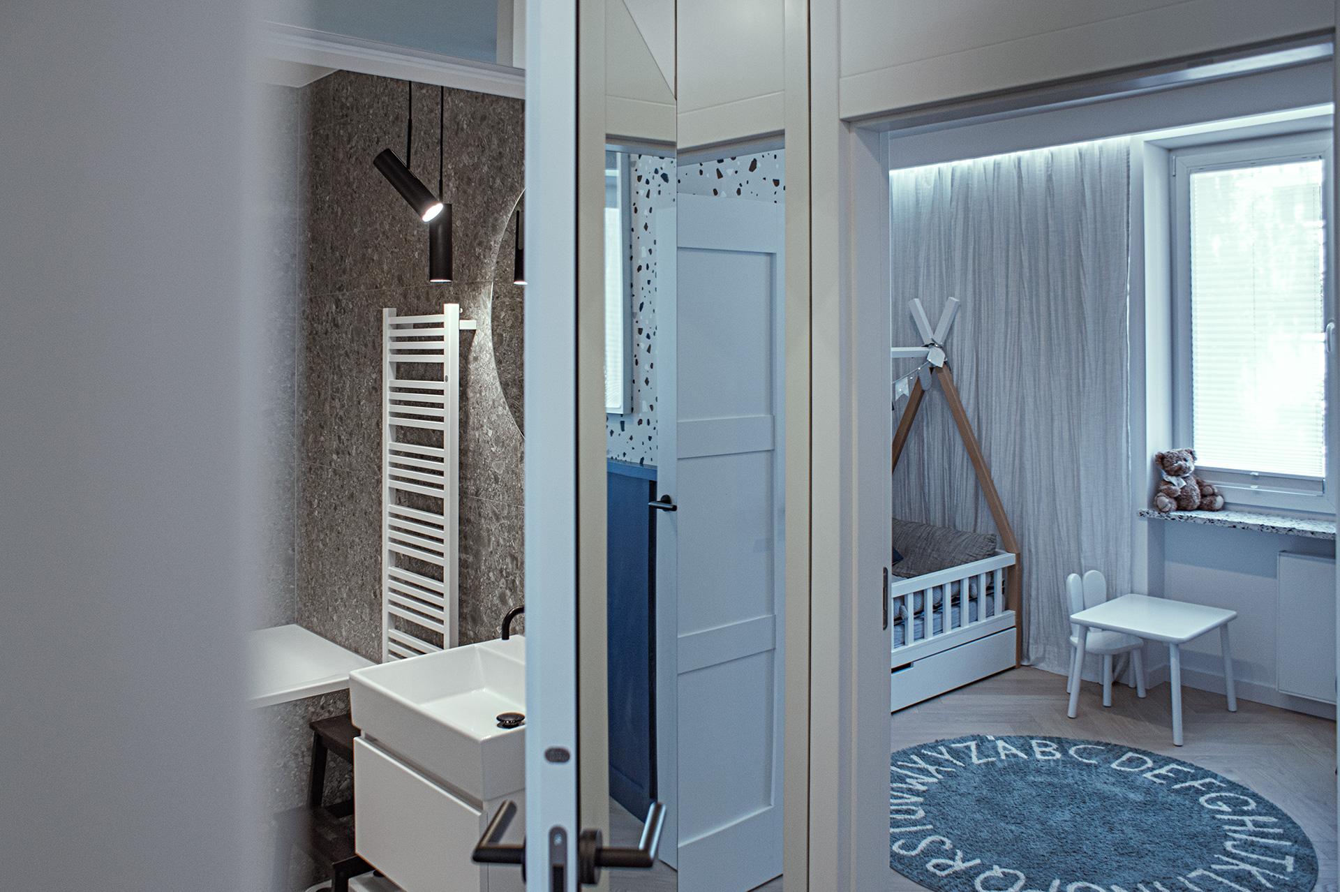 Drzwi do łazienki mają ukrytą ościeżnice – a dzięki lustrzanej oprawie, niemal całkowicie ukryte są przed okiem.
