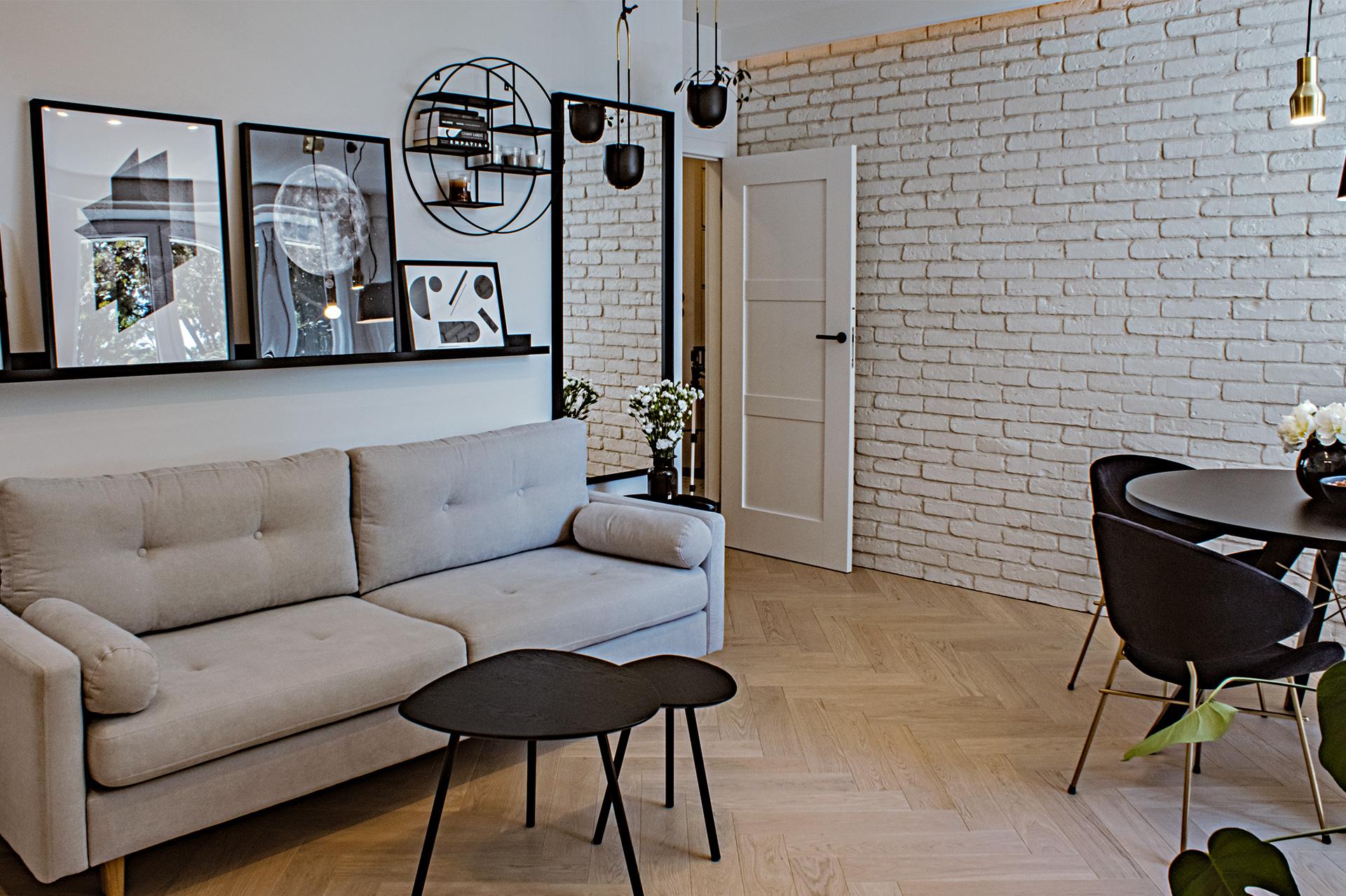 Ściana z białej cegły to detal charakterystyczny dla warszawskiej architektury. Stała się ona główną ozdobą salonu. Pod sufitem zamaskowane, dekoracyjne oświetlenie pomaga ją dobrze wyeksponować.