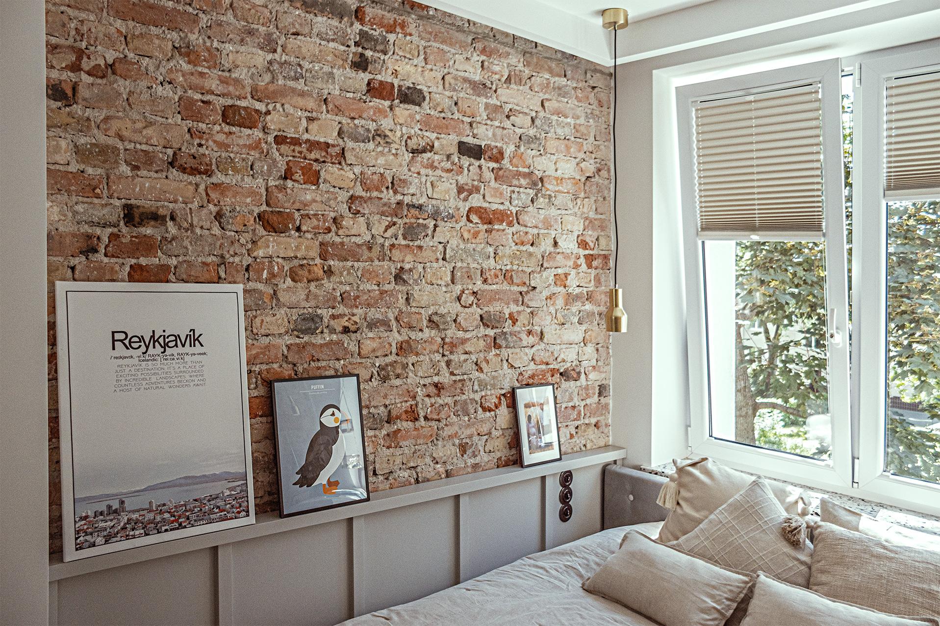 Aby nieco złagodzić surowość cegły, przy łóżku zaplanowałyśmy jasnoszarą boazerię, zakończoną galeryjną półeczką.