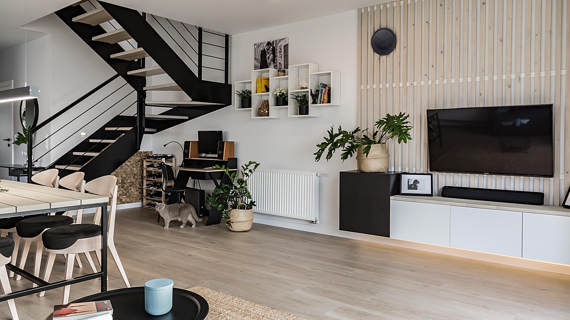 Parter zajmuje obszerny salon z dużym aneksem kuchennym, jadalnią i klatką schodową prowadzącą na piętro.