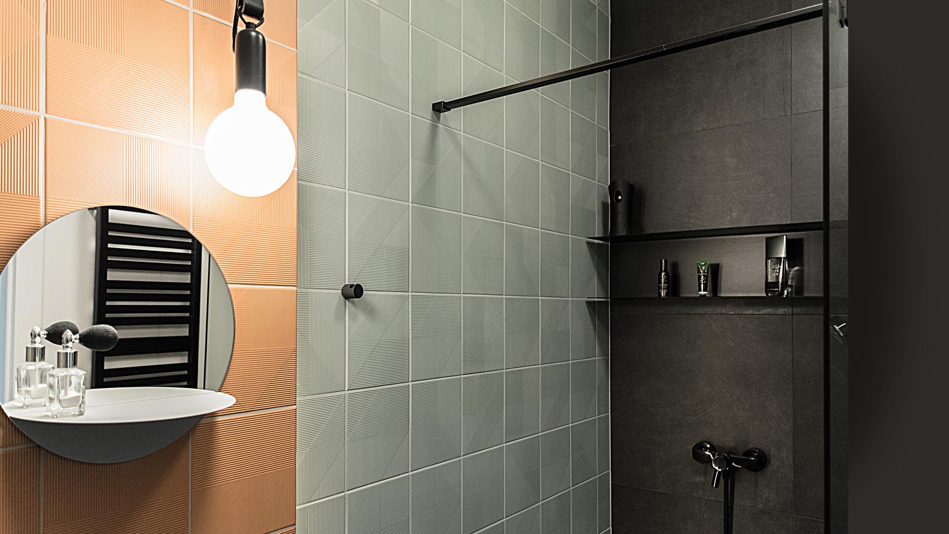 Ściana łazienki pokryta jest strukturalnymi płytkami w trzech modnych kolorach: dyniowym, miętowym i grafitowym.