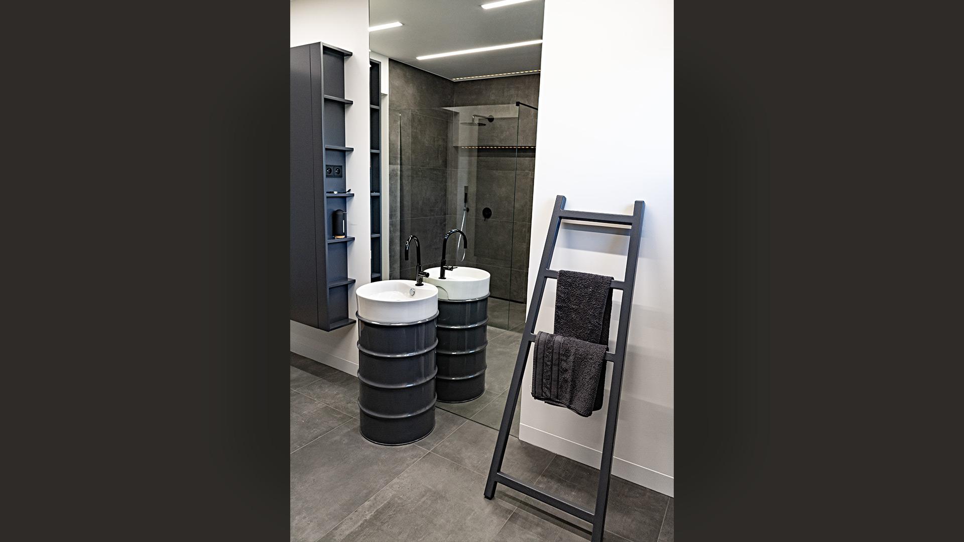 Łazienka dla gości zaaranżowana jest niebanalnie. Umywalka zainstalowana jest na metalowej beczce lakierowanej na czarno. Za nią znajduje się wysokie lustro wklejone w ścianę. Szafa, mimo że jest duża i ciemna, nie przytłacza, bo została powieszona na ścianie.