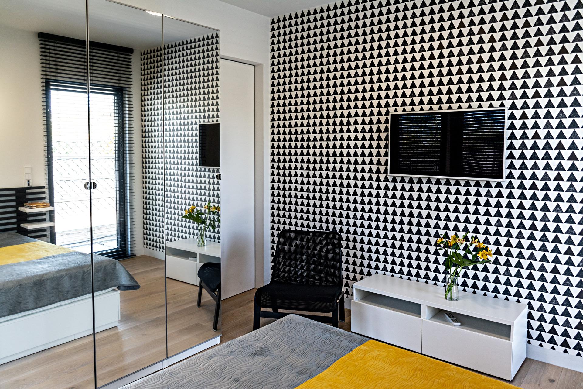 Ściana z tapetą to mocny, graficzny akcent, który nadaje charakteru.  Szafy z lustrzanymi frontami są pojemne i optycznie powiększają przestrzeń.