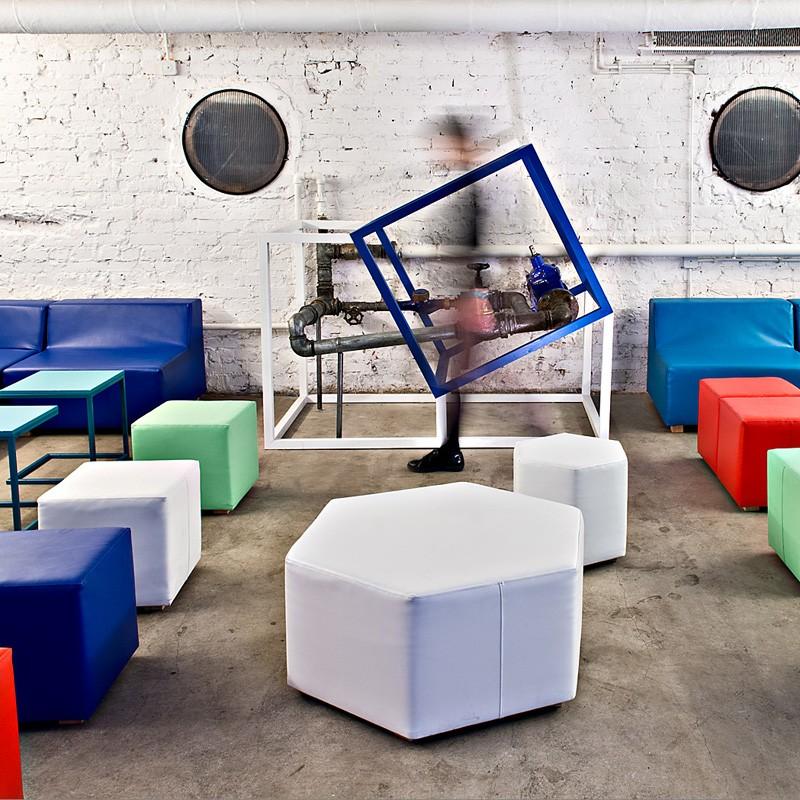 Adaptacja dawnego schronu, niskiego i ciemnego pomieszczenia – na potrzeby klubu z użyciem kolorowych tapicerowanych mebli