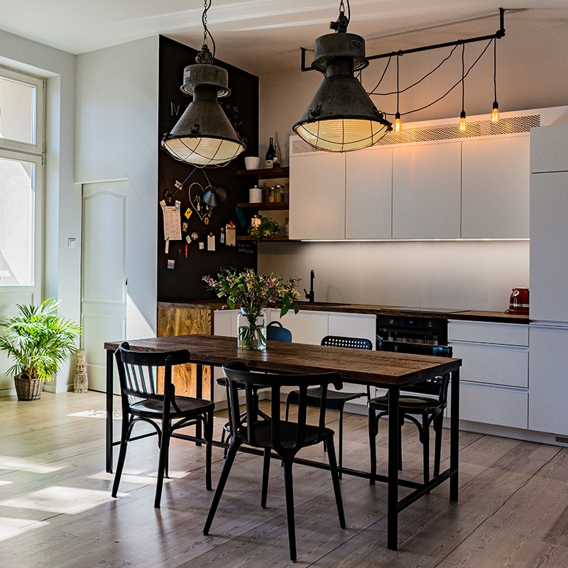 Renowacja aneksu kuchnego w mieszkaniu w stuletniej kamienicy: industrialne lampy, naturalne deski, odnowione podłogi – dla małżeństwa artystów