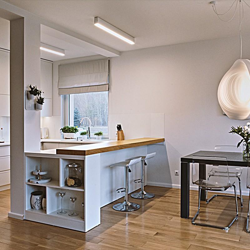 Architekci wnętrz zaprojektowali wnętrza rodzinnego domu podmiejskiego, asną kuchnią, salonem z kominkiem i wygodnymi łazienkami